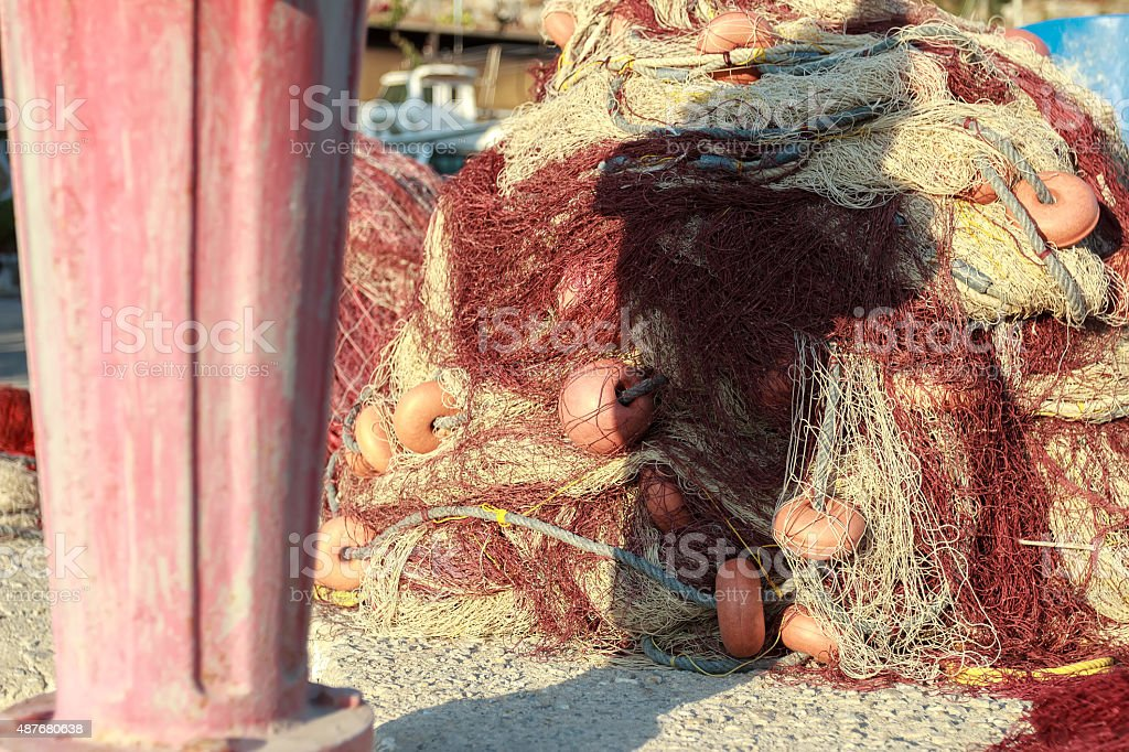 Heap of fishing net with floats on Vathys bay pier stock photo