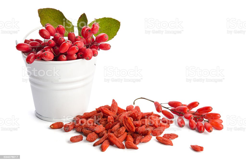heap of goji berries near bowl of berberries stock photo