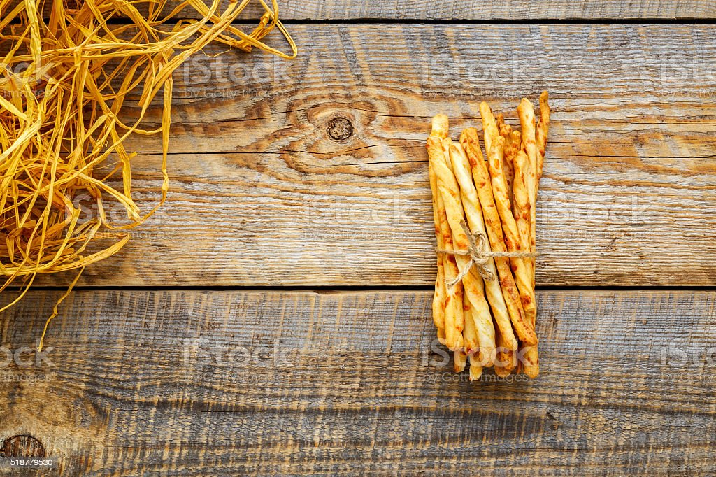 Heap of homemade bread sticks on wooden table with straw stock photo