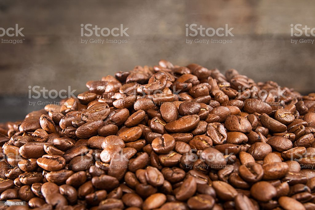 Heap of hot roasted coffee beans with steam stock photo