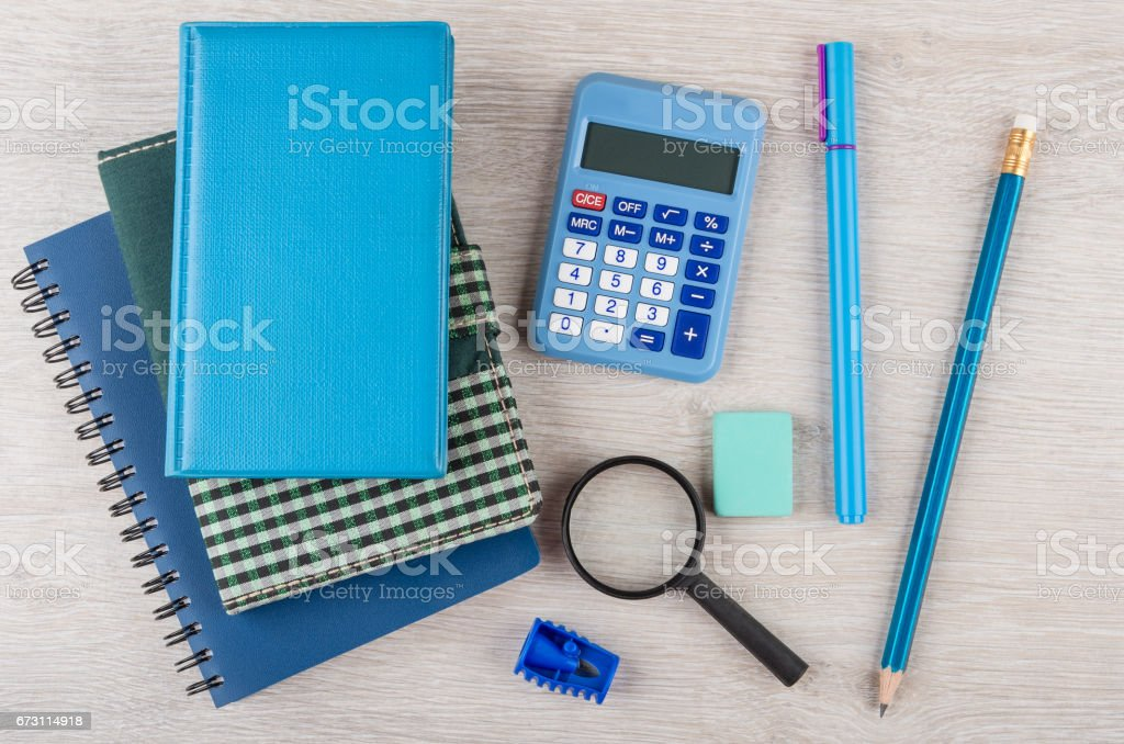 Heap of notepads, calculator and other stationery tools on table stock photo