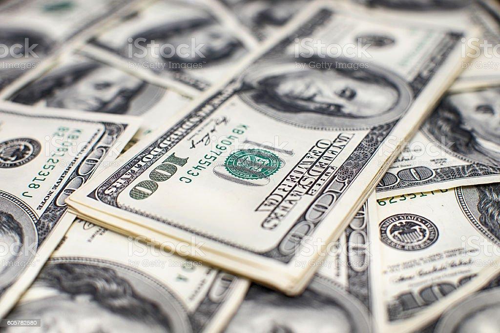 Heap of one hundred dollar bills on money background. Shallow stock photo