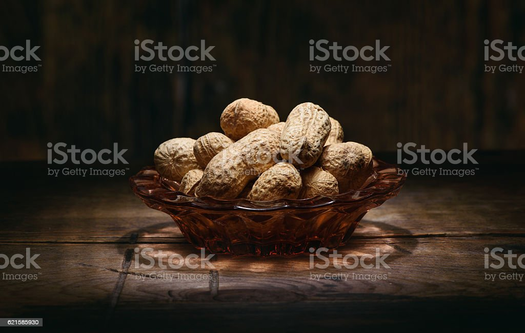 heap of peanuts on rustic wooden table stock photo