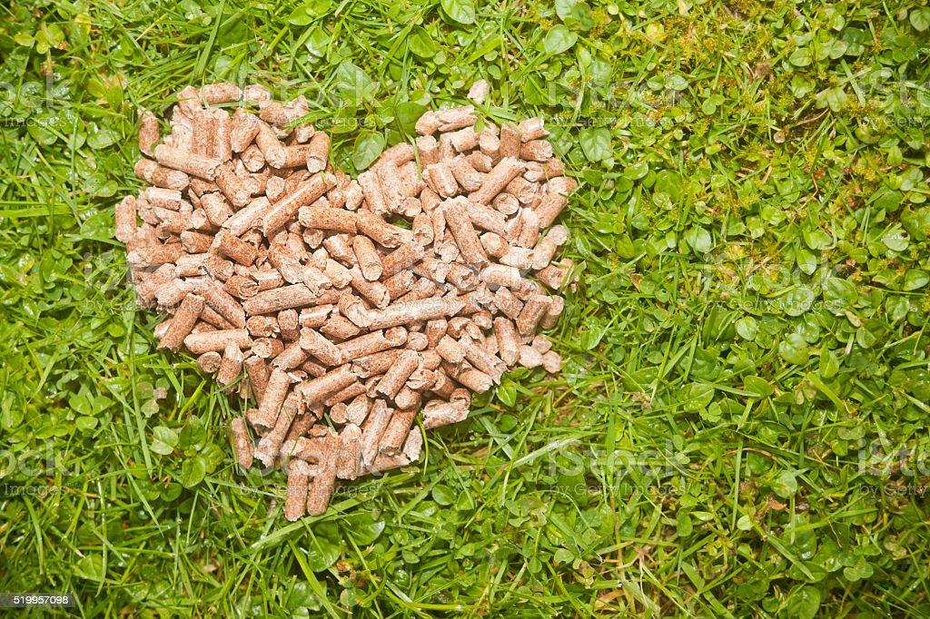 Heap of pellets in heart shape on green grass. stock photo