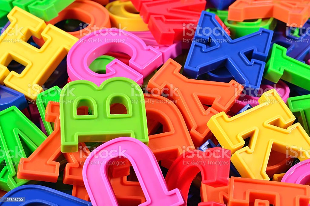 Heap of plastic colored alphabet letters close up stock photo