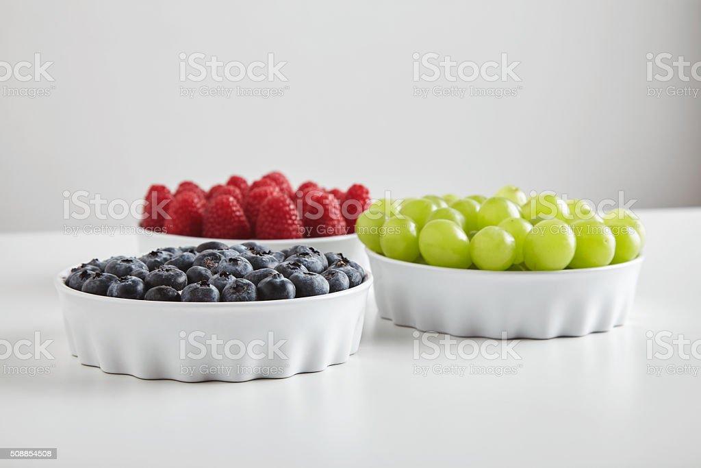 Heap of ripe raspberries blueberries grapes in ceramic bowls stock photo