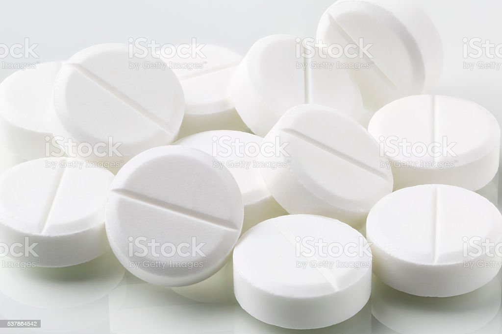 Heap of round white pills and drugs stock photo