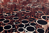 Heap of shiny copper pipes with selective focus effect. 3d