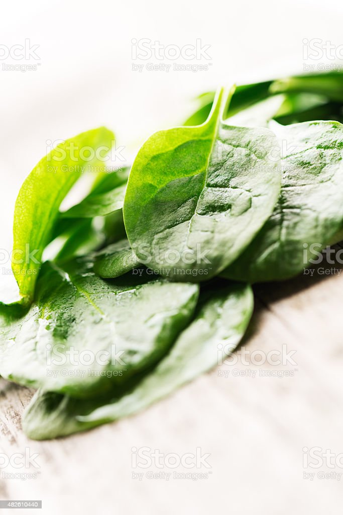 Heap of spinach leaves on wooden background macro stock photo