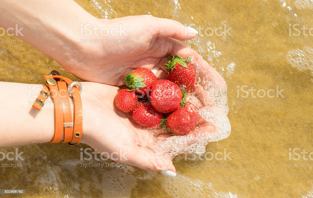 Heap of strawberries in the female palms arms in waterflow stock photo