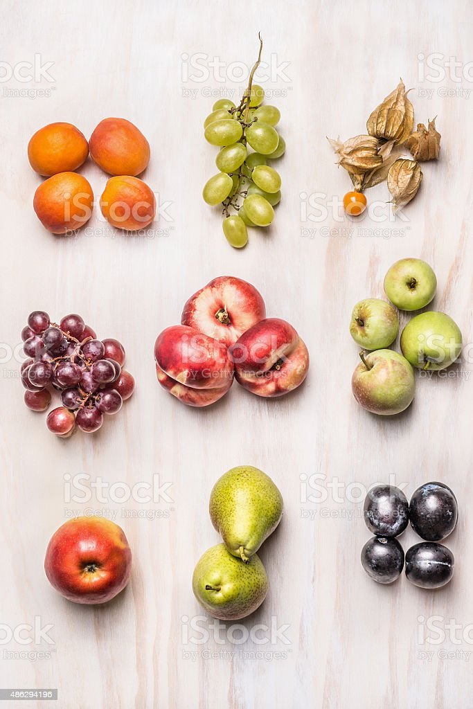 heaps of fresh summer fruits on  white wooden background, stock photo