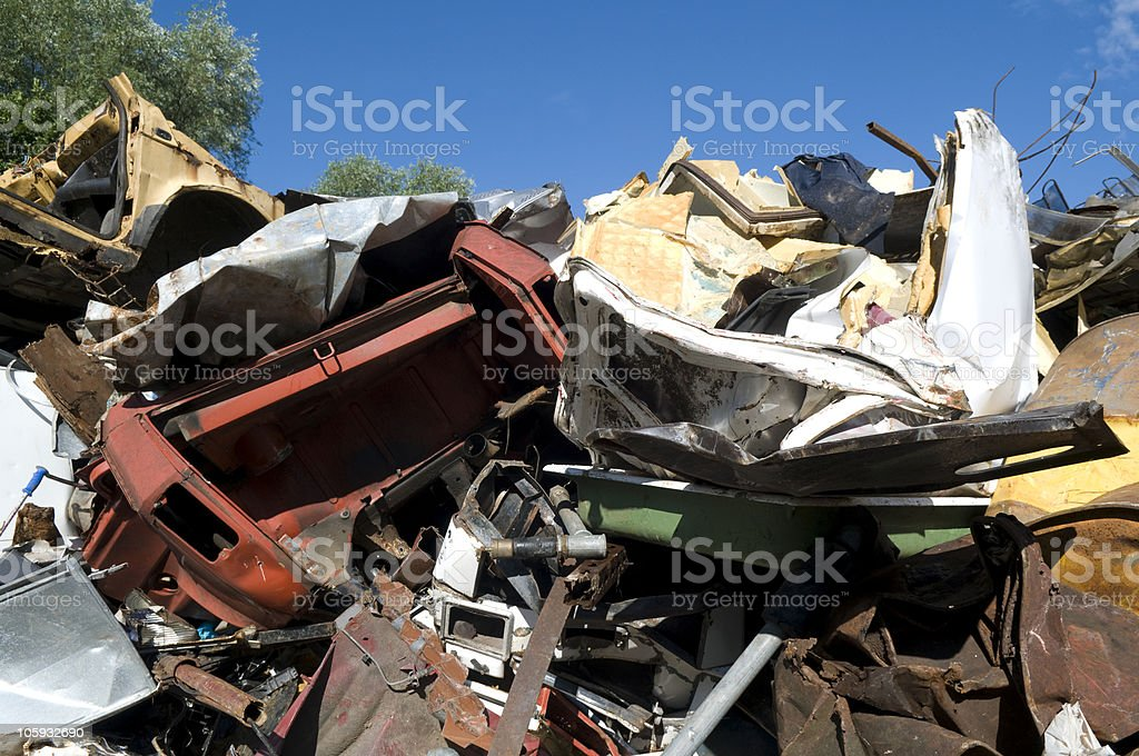 Heaps of metal waste under beautiful blue sky. royalty-free stock photo