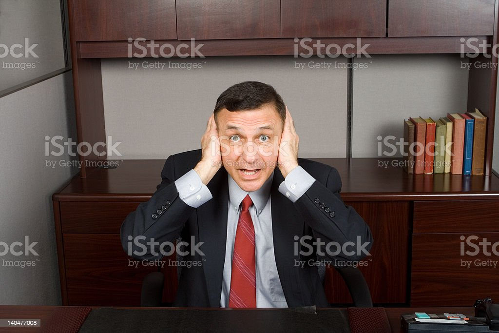 Hear No Evil - White Businessman Covering Ears Desk stock photo