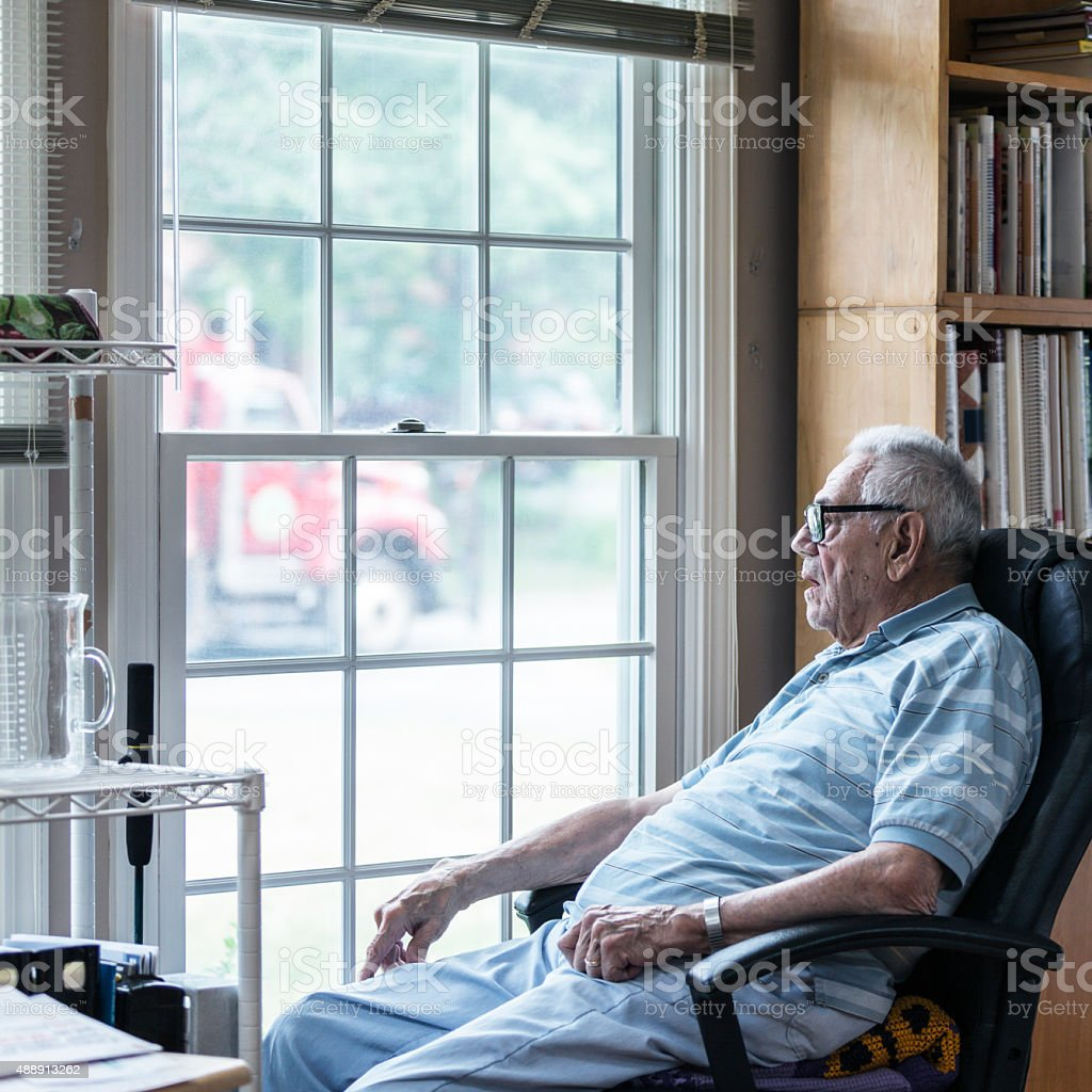 Hearing Impaired Senior Adult Man Looking Through Window stock photo