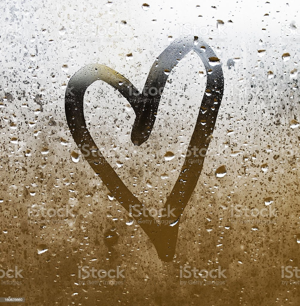 Heart drawn in rain fog on glass stock photo
