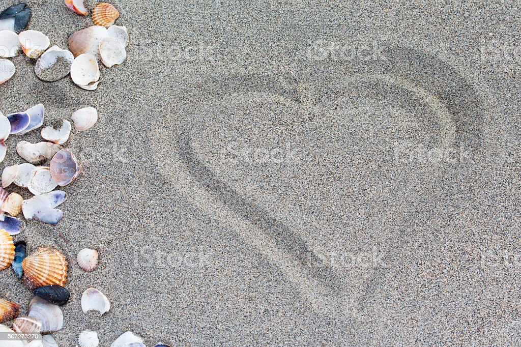Heart drawn in the sand. Beach background. stock photo