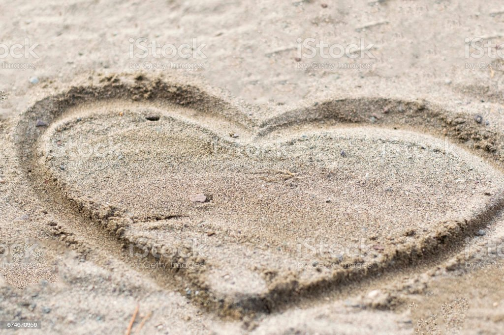 Heart drawn in the sand. Beach background. Top view stock photo