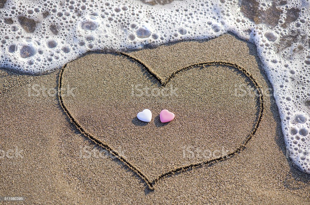 Heart drawn in the sand with two hearts stock photo