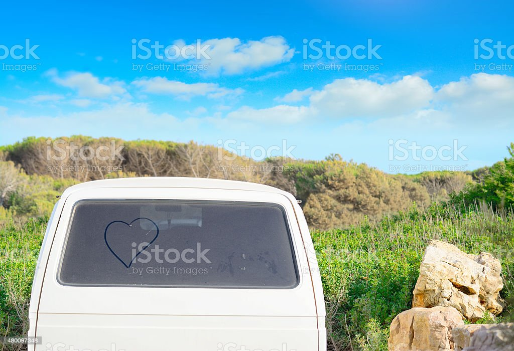 heart drawn on a dirty back window in the summertime stock photo