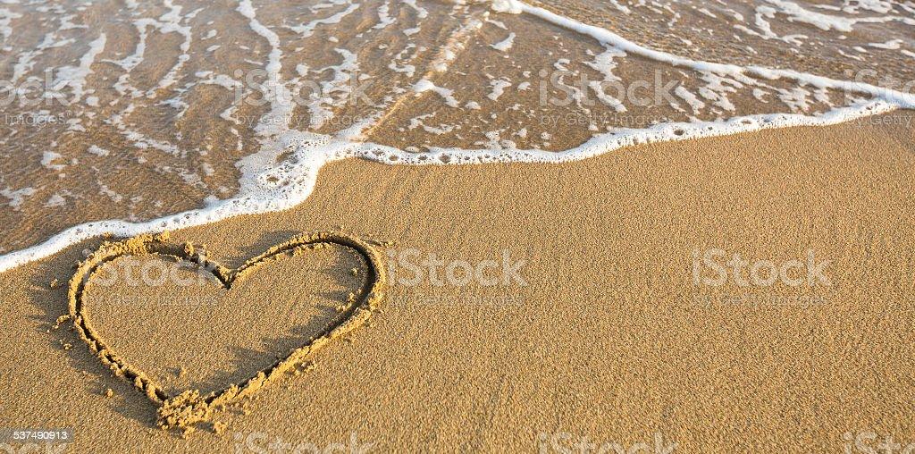 Heart drawn on ocean beach sand. stock photo