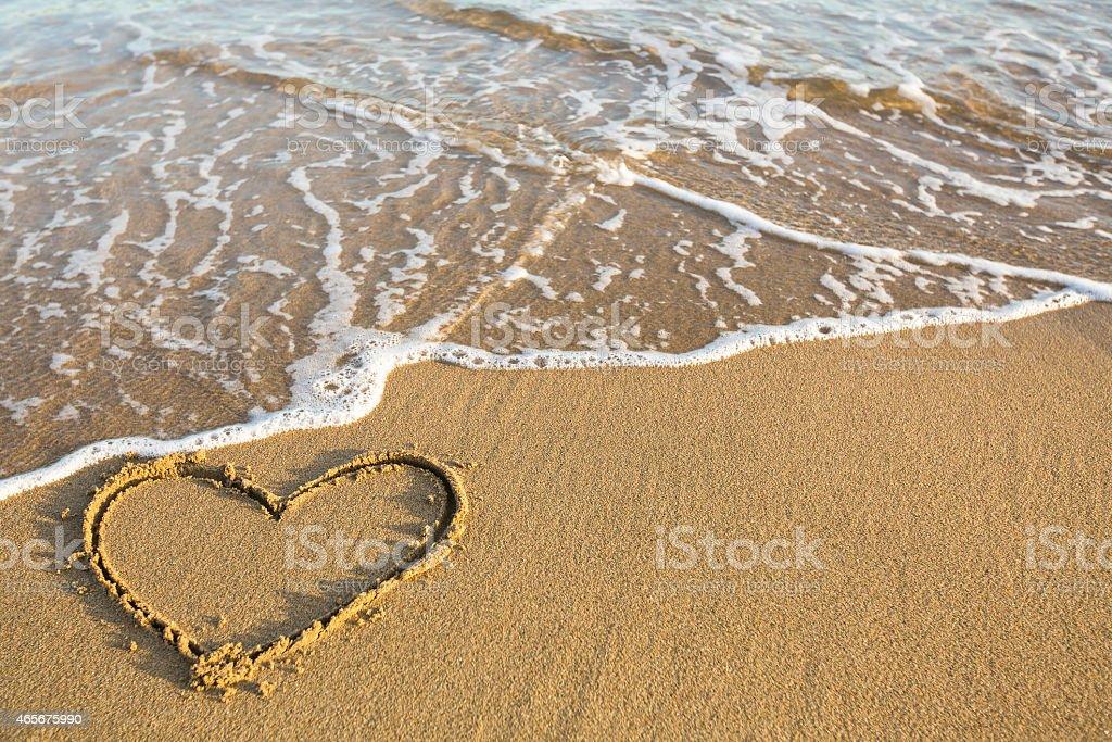 Heart drawn on the sand of a sea beach. stock photo