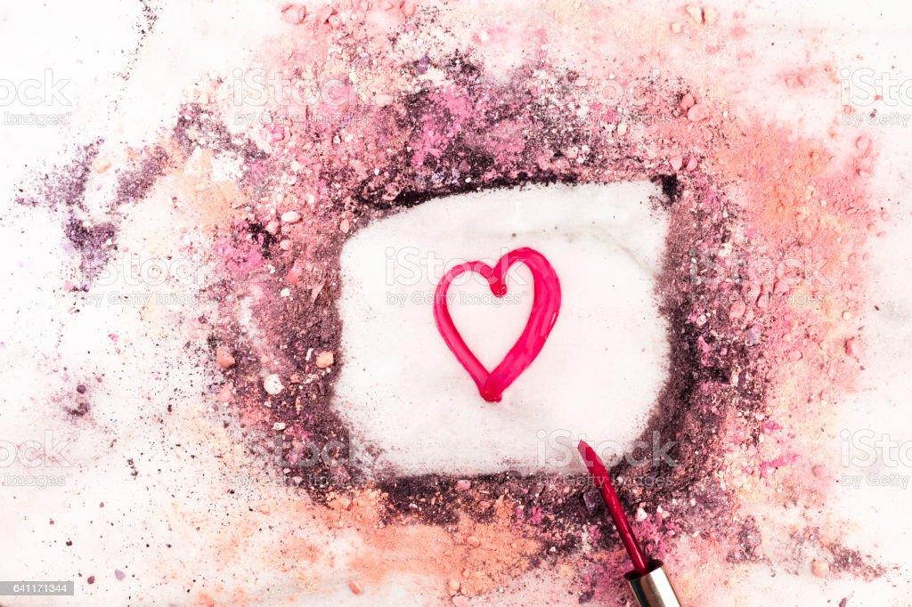 Heart drawn with lipgloss and makeup powder stock photo