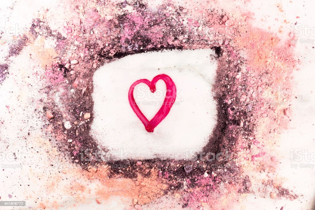 Heart drawn with lipstick within frame of powder stock photo
