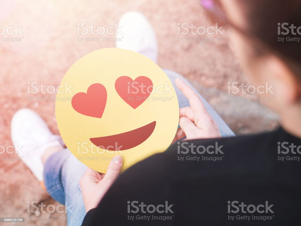 Heart emoticon in hand. Smitten young woman holding printed paper or cardboard love smiley face. Happy Valentine's day   or anniversary theme. Creative communication. Being in love or having a crush concept. stock photo
