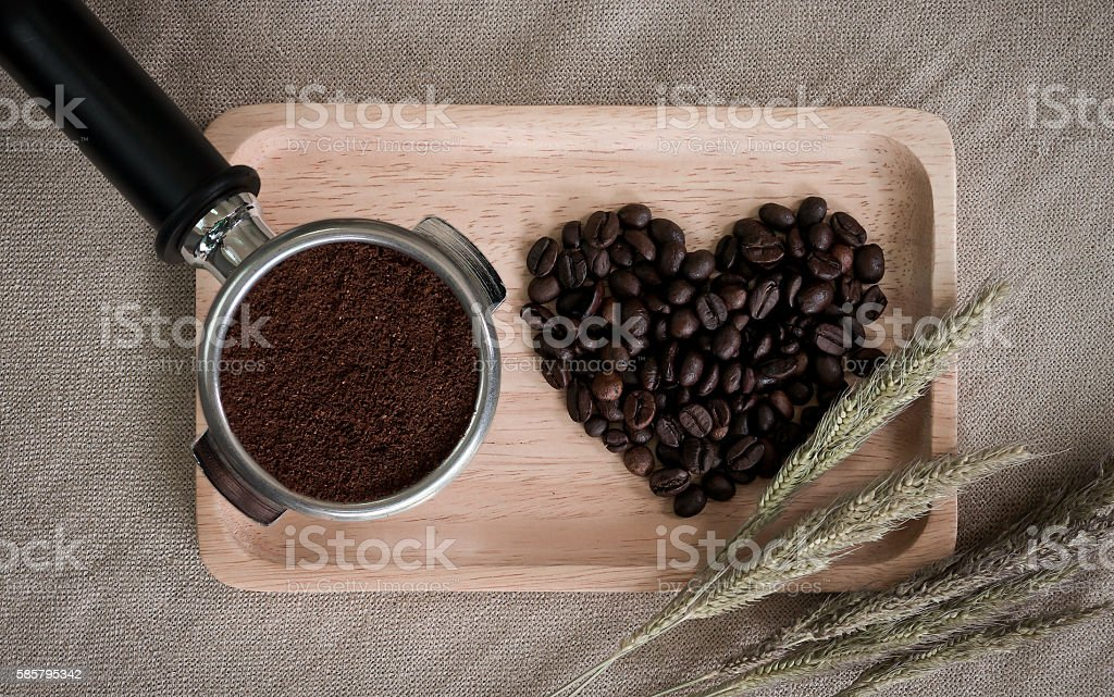heart from coffee beans and wooden spoons with coffee maker stock photo