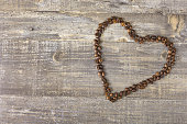 Heart from coffee beans wooden background Beautiful textured table