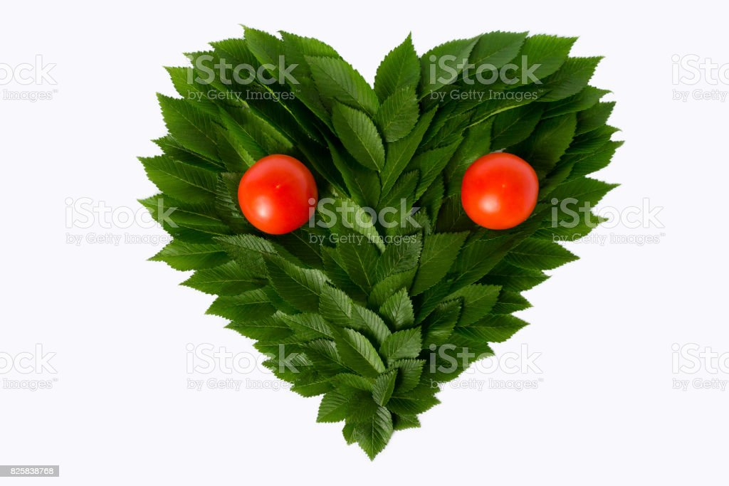 Heart from green leaves with tomatoes. Still life resembles a face. The concept of love of nature and rational nutrition stock photo