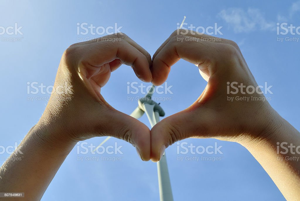 Heart from hands with a wind turbine in the background stock photo
