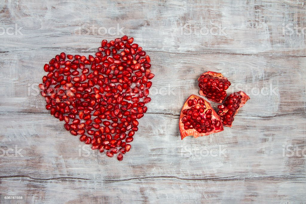 Heart from pomegranate grains on wooden background stock photo