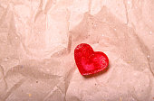 Heart from red ice on the crumpled packing paper