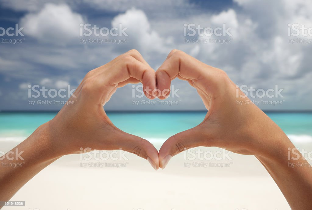Heart gesture with hands at beach stock photo