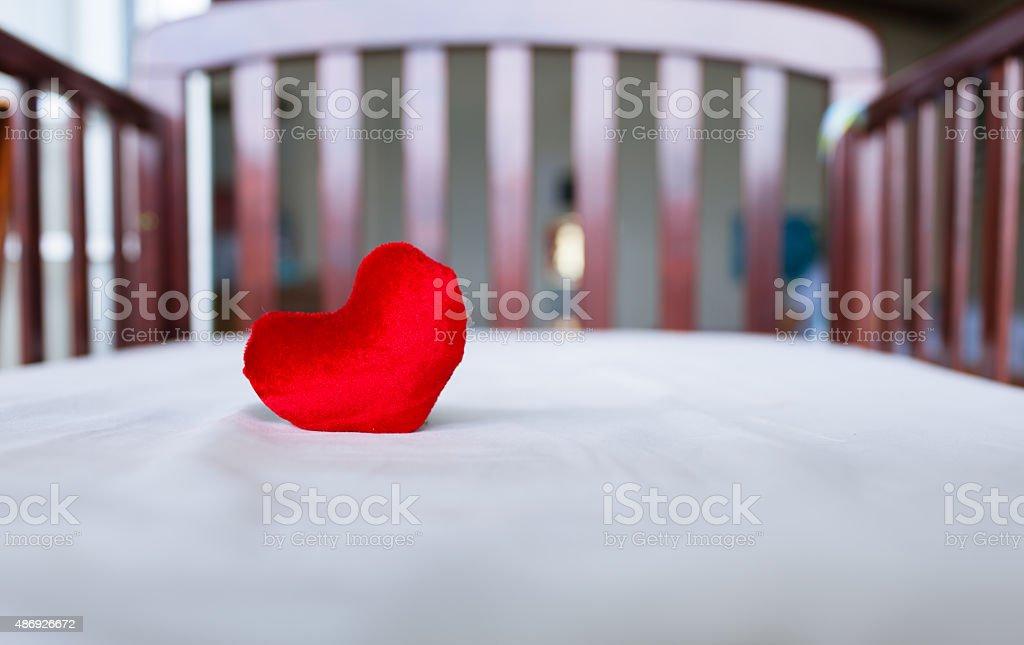 Heart in baby's crib stock photo