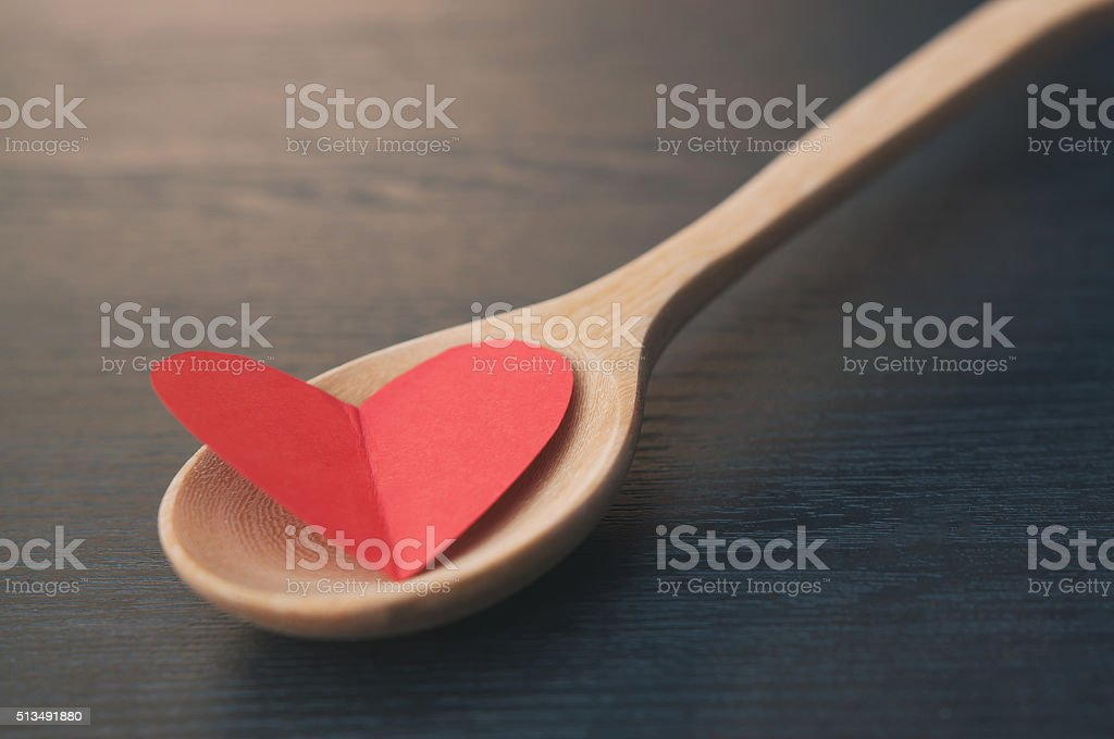 Heart is in a wooden spoon like some food. stock photo