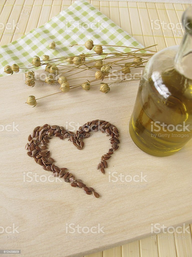 Heart made of linseed and bottle of flaxseed oil stock photo