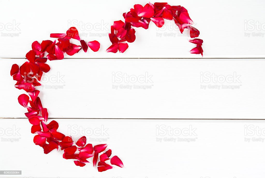 heart made of petals on wooden surface stock photo