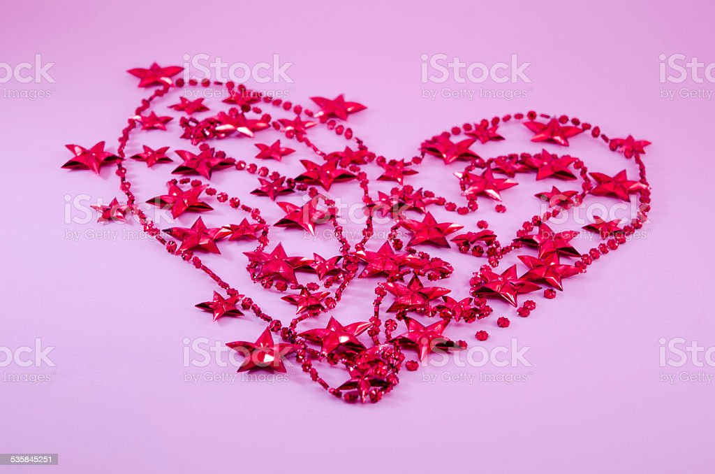 Heart made out of red Christmas tree pearls and stars royalty-free stock photo