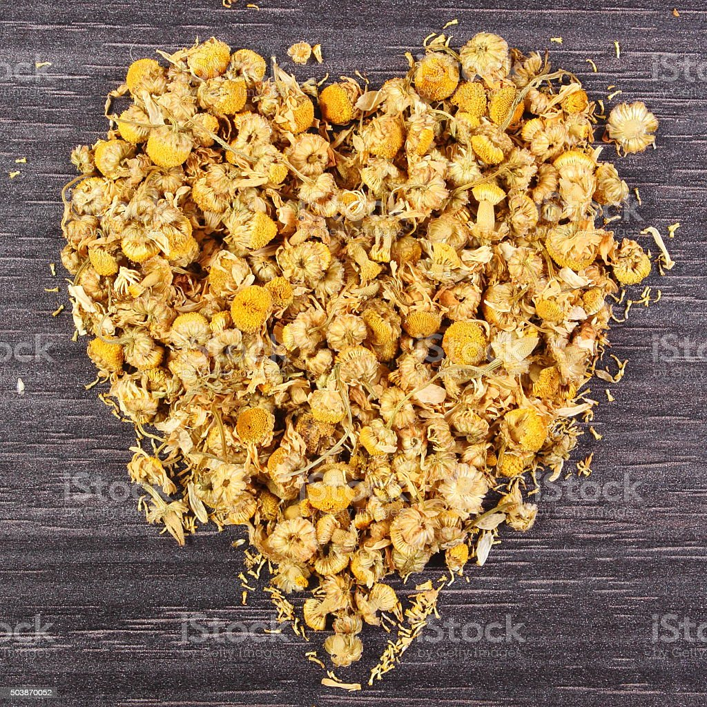 Heart of dried chamomile on wooden table, alternative medicine stock photo