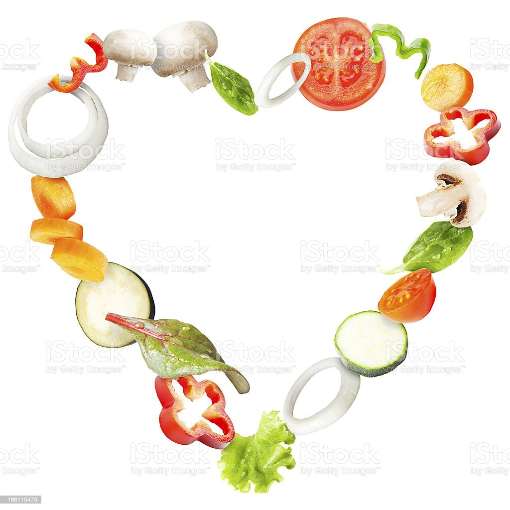 Heart of fresh vegetables flying in a plate stock photo