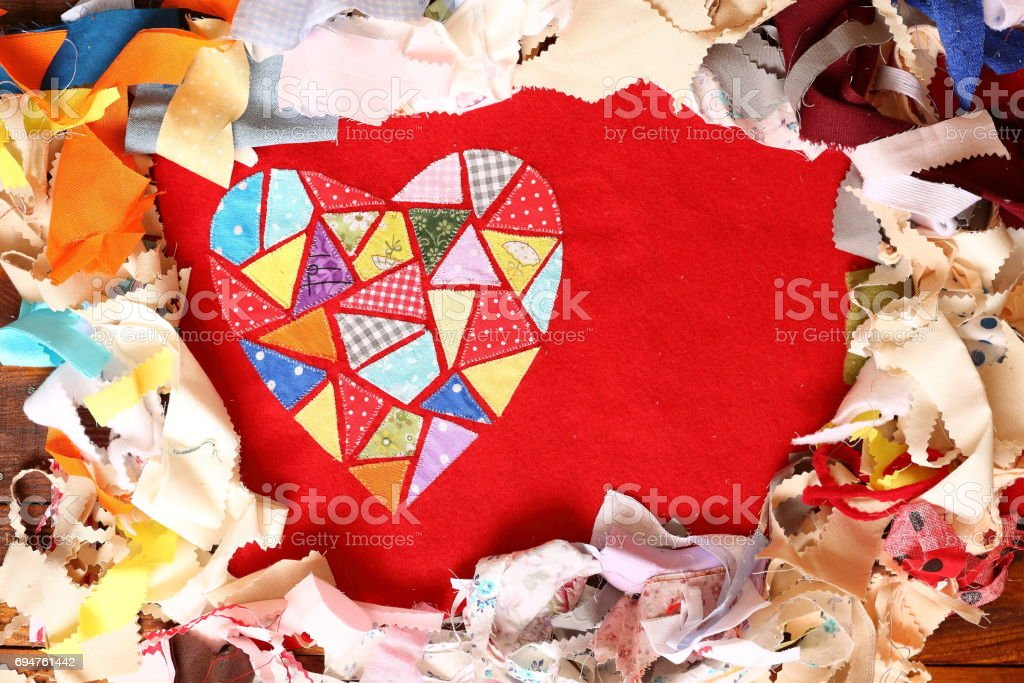 Heart of multicolored embroidered patches on red cloth on multi-colored pieces of fabric background. Love, romance and creativity stock photo