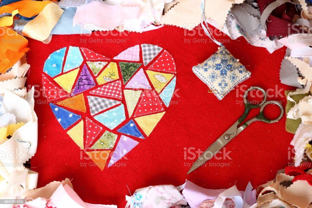 Heart of multicolored embroidered patches on red cloth, scissors and needle bar on multi-colored pieces of fabric background. Love, romance and creativity stock photo