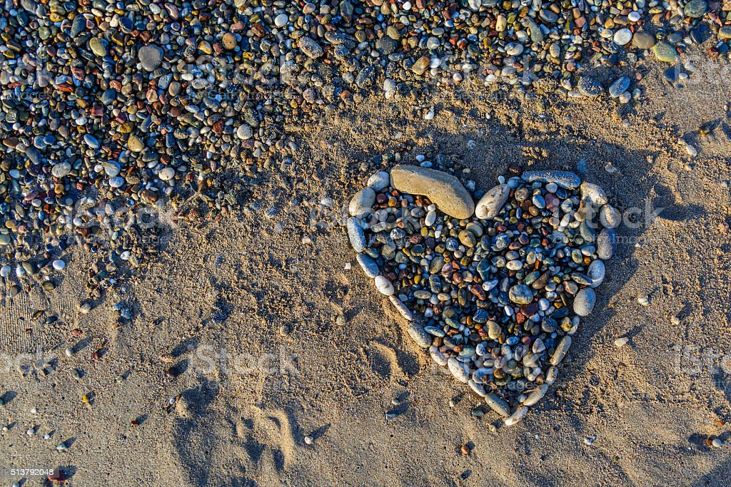 Heart of pebbles on golden and soft sand on beach stock photo