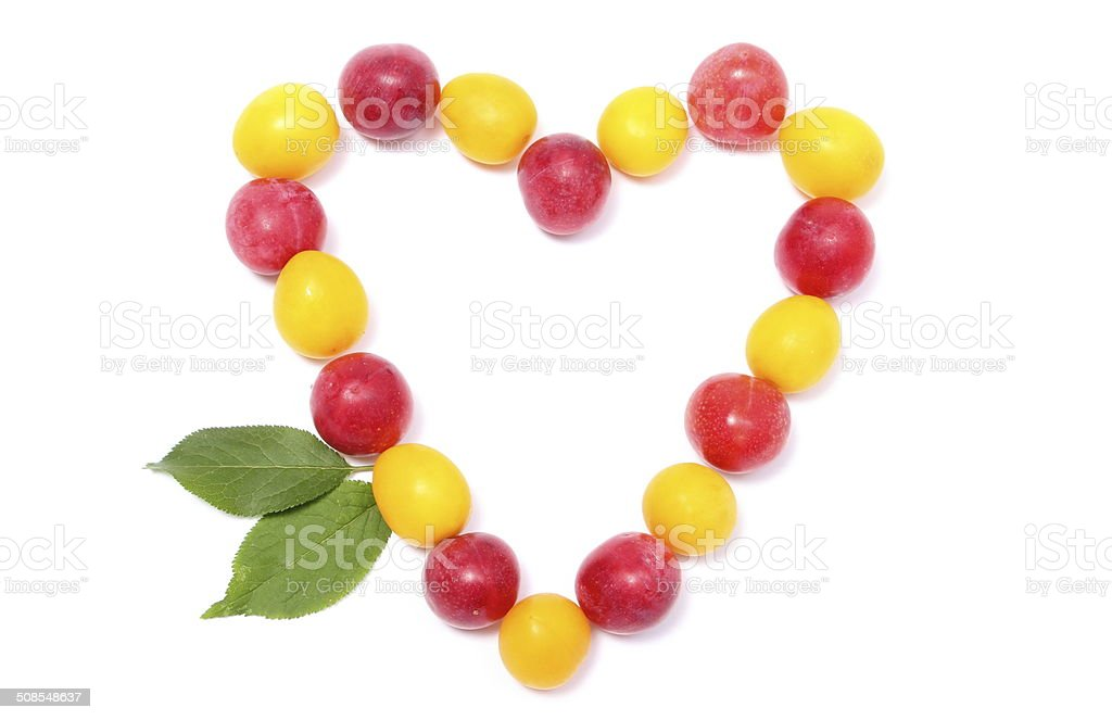 Heart of red and yellow mirabelle on white background stock photo