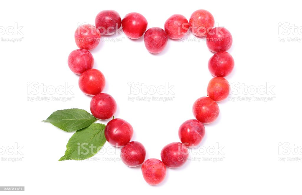 Heart of red mirabelle on white background stock photo
