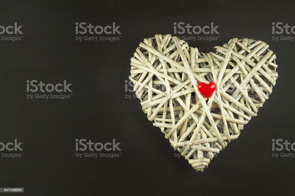 Heart of wicker on wooden background. Symbol of love. stock photo