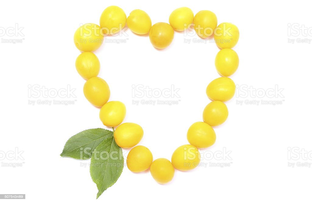 Heart of yellow mirabelle on white background stock photo
