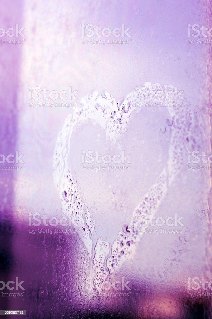 heart on a wet window glass stock photo